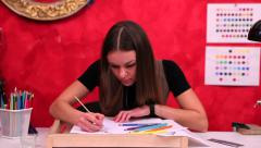 Young woman metal artist draws a sketch decoration in studio (dolly shot) - stock footage