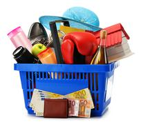 Variety of consumer products in plastic shopping basket isolated on white Stock Photos
