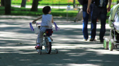 Child on bike in the park Stock Footage