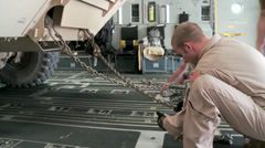 Securing chains on the C-17 Globemaster III operations Stock Footage