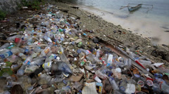 Garbage washed up on beach including plastic bottles and cartons Stock Footage
