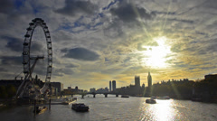 boats passing thames river with sunset silhouette london skyline of eye, big ben - stock footage