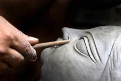 an artisan creating head of clay idol - stock photo