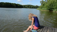 Stock Video Footage of girl sitting on bridge large lake slosh water feet sunny day