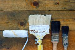 used paintbrushes and roller on old wooden table - stock photo