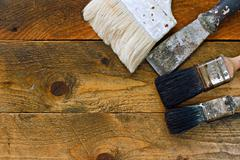 used paintbrushes and scraper on old wooden table - stock photo
