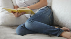 Pretty girl sitting on sofa reading book looking at camera and smiling. Pannig Stock Footage