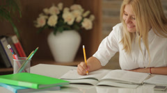 Cheerful girl sitting at table with books studying writing in notebook and sm Stock Footage