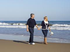 romantic mature couple walking along the beach - stock photo