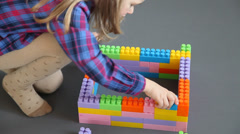 Little girl playing with construction set, grey background Stock Footage