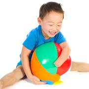 Chinese boy with light handicap playing with beach ball Stock Photos