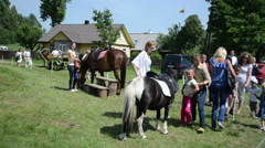 Parents ride their kids on pony and horse for money in festival Stock Footage
