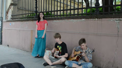Young guitarists play guitar and girl in long skirt sing Stock Footage