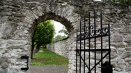 Stock Video Footage of stone entrance with an old medieval black steel gate