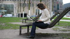 Busy young business woman write to computer, sit on bench in park work hard - stock footage