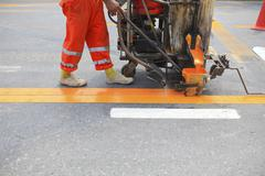 Machine and worker at road construction Stock Photos