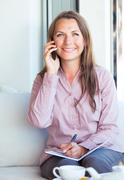 happy businesswoman talking on the phone and writing in organizer in a cafe - stock photo