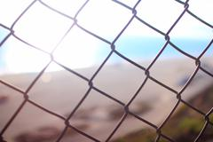 Beach Resort Sunlight and wire fence in Malibu California USA - stock photo