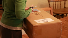 Woman opening package in home Stock Footage