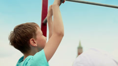 Young boy does chin-ups against Spasskaya tower in Moscow Stock Footage