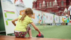 Little girl catches stuffed ball and throws it from behind head Stock Footage