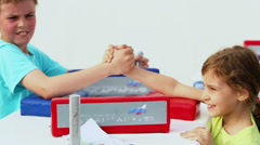 Boy wins arm-wrestling duel with his little sister Stock Footage