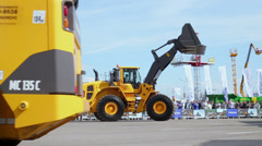 People watch VOLVO machines for building which ride around Stock Footage
