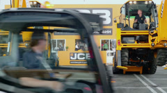 Pair of JCB excavators lift themselves and loader rides during Stock Footage