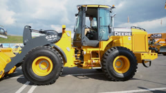 Man raises hands in John Deere tractor which lifts bucket Stock Footage