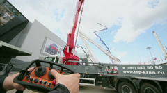 Man holds control unit of crane during Exhibition Stock Footage