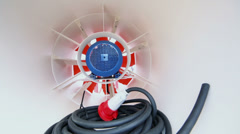 Hank of hose lies at white tube with big fan in metal frame Stock Footage