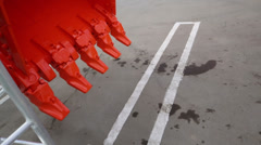 Cogs of orange bucket which moves near asphalt with marking Stock Footage