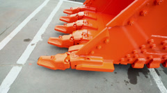 Orange bucket moves near dirty asphalt with marking Stock Footage