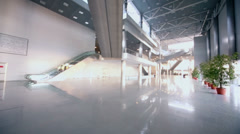 Few people work in large hall of exhibition center Stock Footage