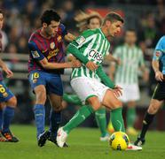 Salva Sevilla(R) of Real Betis vies with Sergio Busquets(L) of FC Barcelona Stock Photos