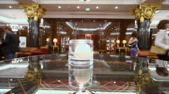 Candle burns on glass table in hall of hotel with people Stock Footage