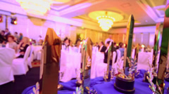 Many golden prizes stand on table at banquet hall with people Stock Footage