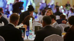 People sit at banquet tables during ceremony of national award - stock footage