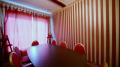Round table for eight persons at small room in red tones Stock Footage