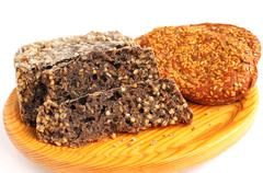 homemade brown bread and buns with sesame seeds on cutting board - stock photo