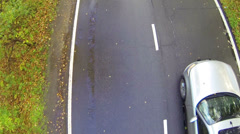 Silvery car moving slowly on two lane street in forest - stock footage