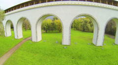 Walking in autumn park with aqueduct during the day Stock Footage