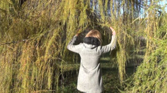 Woman hand part droopy larch thorny branches moves to other side Stock Footage