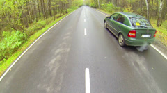 Modern green car driving in forest, above view - stock footage