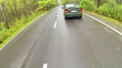 Asphalted wet road with moving car in forest - stock footage