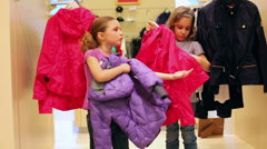 Two girls wear jackets of different colors in the clothing store Stock Footage