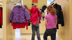 Girl helps to dress in red jacket in the clothing store Stock Footage