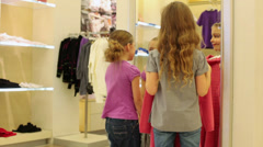 Stock Video Footage of two girls consider clothes in mirror in childrens clothing store