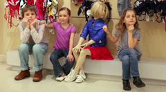 Two beautiful girls and boy posing next to mannequin in clothes Stock Footage