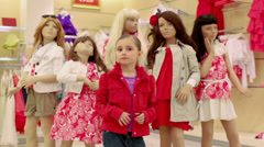 Girl posing against the backdrop of mannequins in clothes Stock Footage